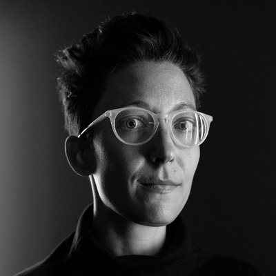 The photo displays a close up portrait shot of Liz Jackson in black and white. She has short hair and is wearing glasses.