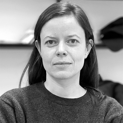 The picture displays a black and white portrait of Irene Posch. She has long hair and is wearing a sweater.